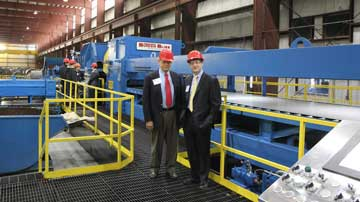 John & Jock Buta in front of a Stretch Leveling Cut-To-Length line